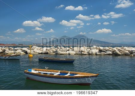 fishing boats in the port of Naples and view of Mount Vesuvius and Gulf of Naples in good weather, Naples, Italy