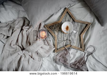 A cup of coffee and a candle in a Scandinavian wooden tray in a cozy bed with a blanket. Knitting a warm woolen sweater on a winter weekend, top view.