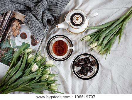 Morning with tea and bouquet of white tulips on a cozy bed