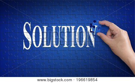 Solution word on Jigsaw puzzle - business concept. Man hand holding a blue puzzle to complete the word Solution divided over them concept of the solution to a problem challenge plan and strategy.