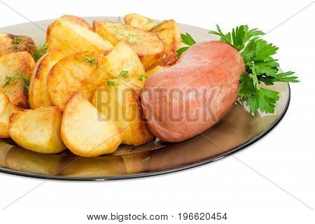 Fragment of the dark glass dish with fried potatoes sprinkled by chopped dill fried wieners and twig of parsley closeup on a light background