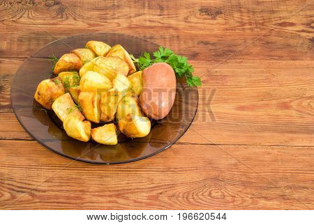 Serving of the country style fried potatoes sprinkled by chopped dill fried wieners and twig of parsley on dark glass dish on a surface of old wooden planks