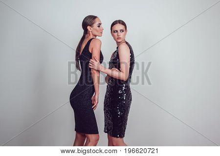 Two beautiful women in black night fashion dress posing on a gray background.