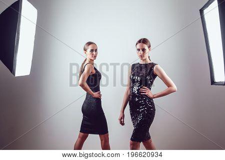 Two beautiful women in black night fashion dress posing in photo studio.