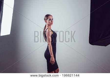Beautiful woman in black night fashion dress posing in photo studio.