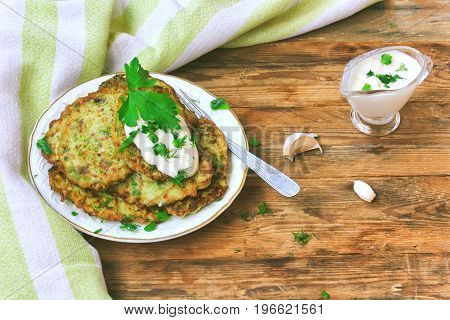 homemade fried fritters of zucchini with sour cream sauce herbs garlic towel on wooden table top view