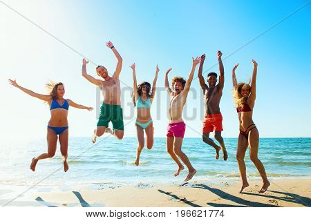 Happy group of friends jumps together on the seashore