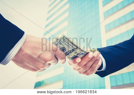 Hands of businessmen passing money US dollar bills - vintage tone