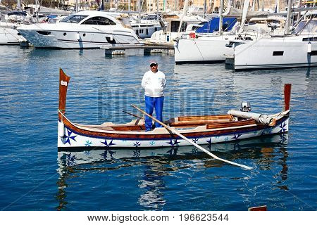 VITTORIOSA, MALTA - MARCH 31, 2017 - Oarsman standing in a traditional Maltese Dghajsa water taxi in the harbour with views towards Senglea waterfront Vittoriosa Malta Europe, March 31, 2017.