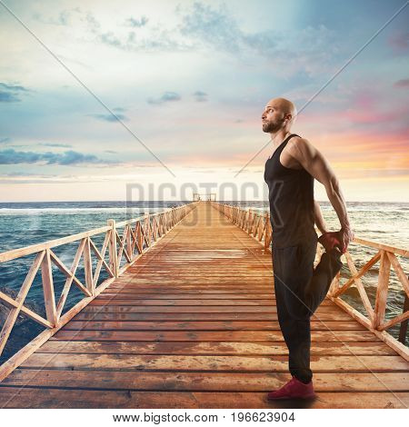 Stretching and exercises of gymnastics on a pier at sunset with sea landscape