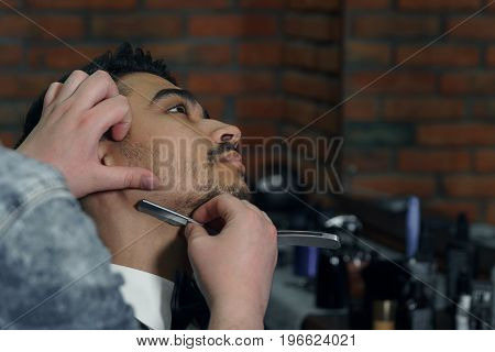 Close-up side view of young bearded man getting beard haircut by hairdresser at barbershop.