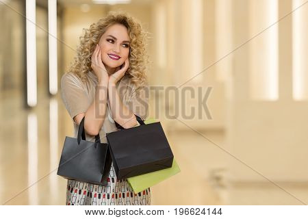 Woman Surprise Holds Cheeks By Hand .beautiful Girl With Shopping Bags Pointing To Looking Right. Pr