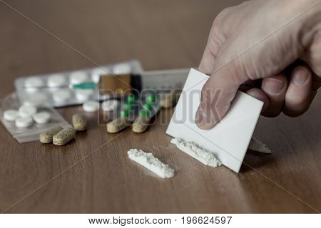 cocaine or other drugs cut with card. hand dividing white powder narcotic. syringe on the wooden table