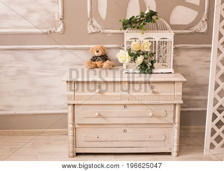 Classic interior of baby room with chest of drawers and teddy bear.