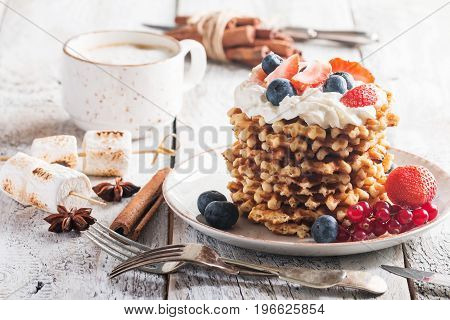 Belgian waffles with creem and fresh berries on white wooden background