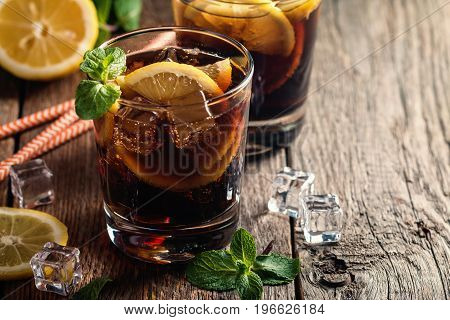 Fresh made Cuba Libre with brown rum, cola, mint and lemon on wooden background