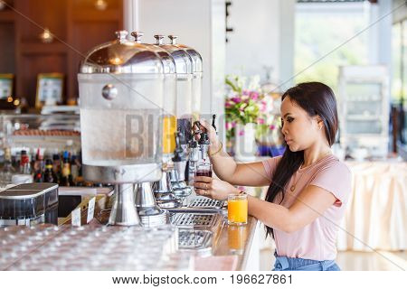 Portrait of beautiful thai asian women hand holding glass and pushing refill orange juice at buffet restaurant Juice buffet self service in morning at hotel.