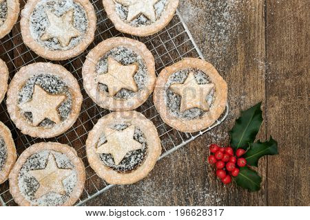 Homemade christmas mince pies on a baking rack with icing sugar dusting, holly and red berries on oak wood background.