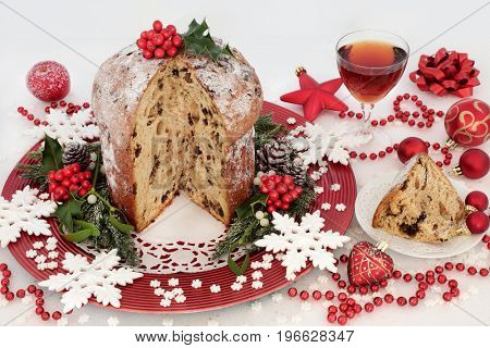 Italian chocolate panettone christmas cake and slice with glass of sherry, snowflake and red bauble decorations, holly, mistletoe, fir and pine cones on white glitter background.