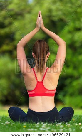 Rear view of young fit healthy woman female or girl practicing yoga pose on a mat outside in a natural tranquil green environment