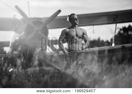 A handsome guy is standing by the plane. Black and white photo.