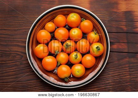 Cherry tomatoes in bowl on wooden table. Top view.