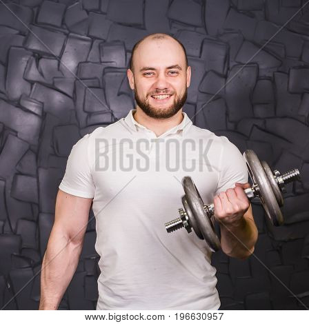 Good looking young man lifting dumbbells and working on his biceps