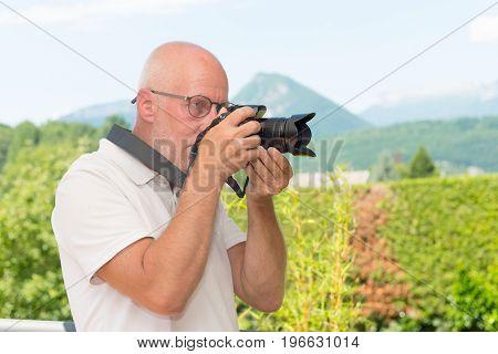 mature man with a dslr camera outdoors