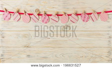 Easter decor. Paper egg with a pink ribbon on a light wooden background. Selective focus.