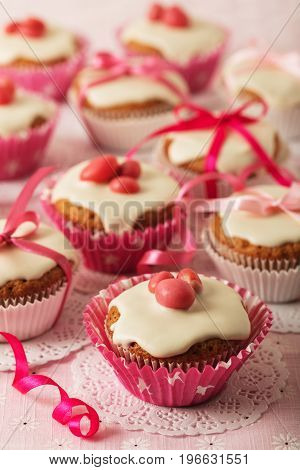 Cupcakes with white icing decorated with pink candy and ribbons. Selective focus.