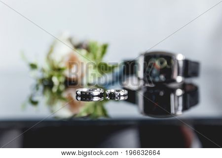 Pair of golden wedding rings with diamond on smooth mirror surface. Boutonniere with a rose flower and a wristwatch on background. The traditional accessories of the groom at the wedding.