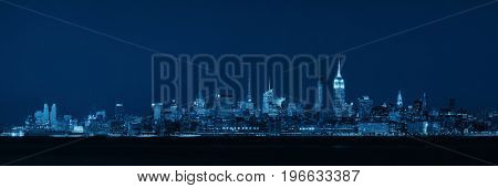 New York City midtown skyline with skyscrapers over Hudson River viewed from New Jersey at night