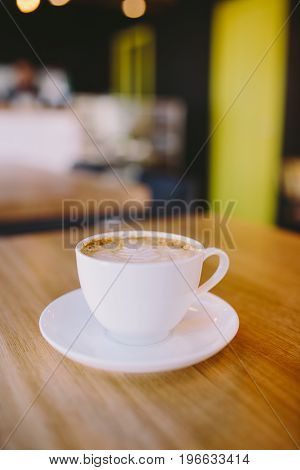 Close up view of white cup of coffee on wooden bar counter