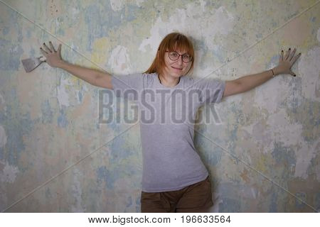 Home renovation - cute red hair woman with scraper near wall glues wallpaper, portrait