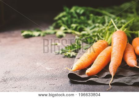 Fresh organic and sweet carrot over dark stone background