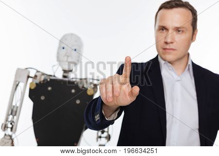 Reach out and touch it. Intelligent distinguished dedicated scientist working in his lab and programming the robot while standing isolated on white background