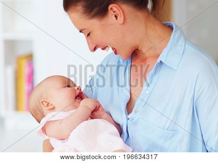 happy young mother enjoying communication with little daughter