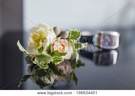 Boutonniere with a rose flower and a wristwatch lie on a smooth mirror surface. The traditional accessory of the groom at the wedding.