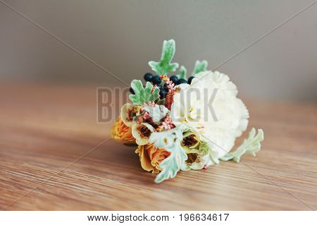 Boutonniere with peony flower on wooden background. The traditional accessory of the groom at the wedding.