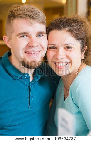 Portrait of laughing caucasian couple enjoying date in cafe.