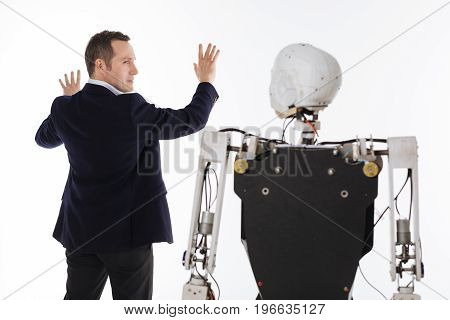 Testing software. Motivated inspired intelligent man working in his lab and developing artificial intelligence while applying his programming on the robot