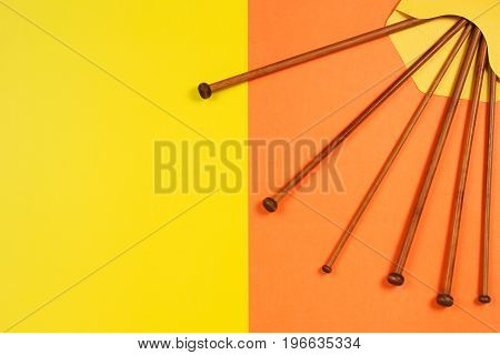 Variety of wooden knitting needles in envelope on yellow and orange background