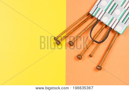 Wooden knitting needles on yellow and orange background. Top view