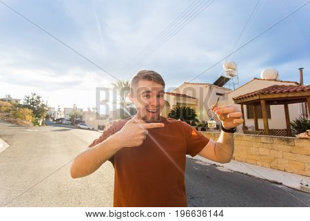 Young smiling man showing key to new home - Concept of housewarming, real estate, tenant and new home.