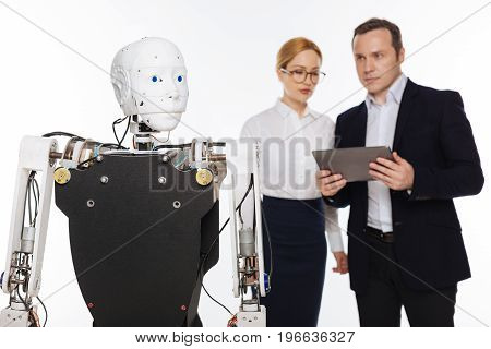 Elaborate machine. Enthusiastic bright creative scientists working in a lab and asking his colleague monitoring the experiment while adjusting new setting to his robot