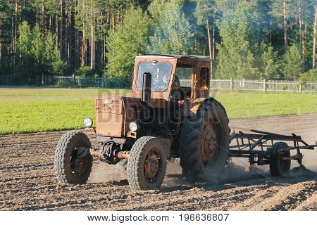 Preparing land with seedbed cultivator - tractor on field, agricultural works at farmlands, telephoto