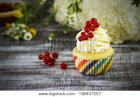 Delicious cupcakes with berries on a dark background with flowers