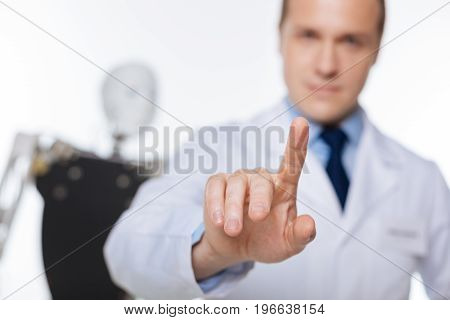 On the tip of a finger. Doted focused hardworking man using contemporary technologies for developing software for robots while working in a lab
