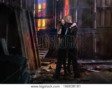 The guy kisses the girl. Couple with arms. The old hangar - shelter from the fire