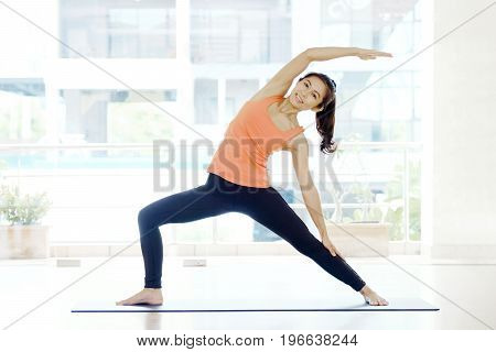 Asian woman practicing yoga fitness stretching flexibility pose working out healthy lifestyle wellness well being wearing sportswear black pants bra indoor full length studio background